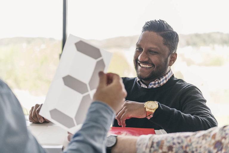 Glad säljare i kontorslandskap diskuterar värmetransfer