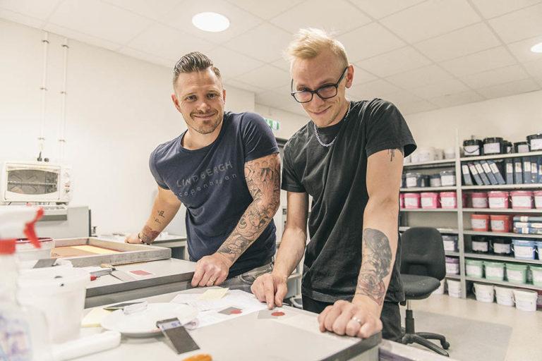 Två glada prepress-medarbetare kontrollerar färger i färgrummet innan produktion