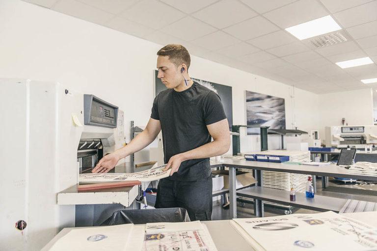 Medarbetare på kvalitetsavdelningen skär ut transfertryck i en skärmaskin