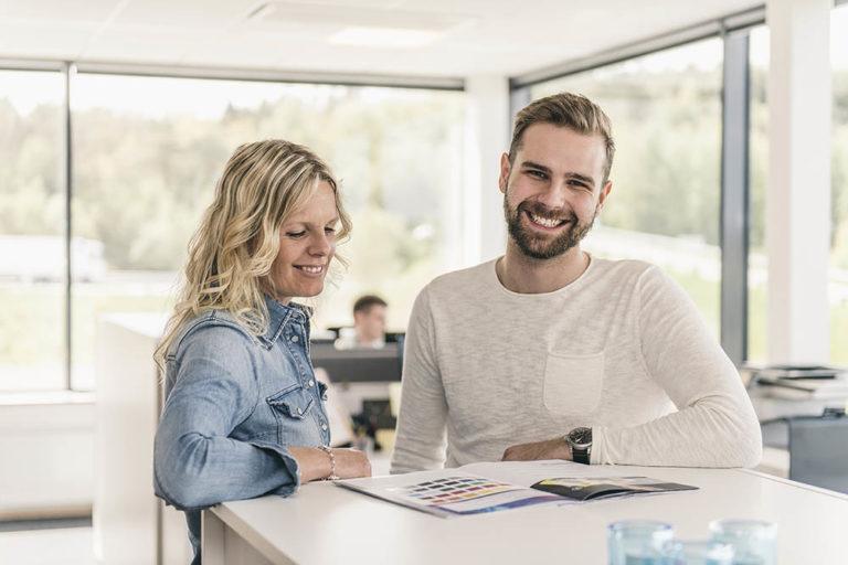 Två glada kundtjänstmedarbetare i kontorslandskap