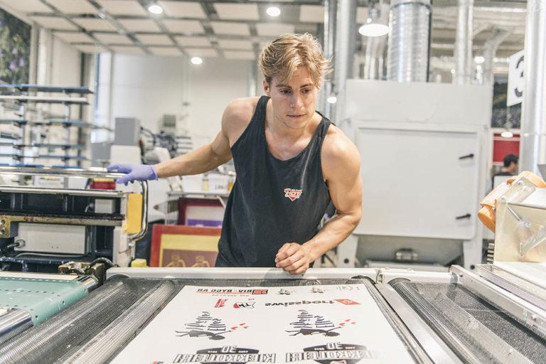 Tryckerimedarbetare kontrollerar transfertryck i maskin efter produktion